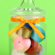 Stock Photo: Glass jar containing various colored ribbons on green background