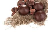 Шоколадные конфеты и какао-бобов, изолированные на белом фоне — Стоковое фото