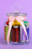 Glass jar containing various colored thread on lilac background — Stock Photo