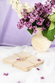 Composition with lilacs on light fabric background — Stock Photo