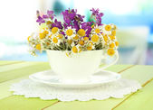 Bouquet of chamomile flowers in cup, on bright background — Stock Photo