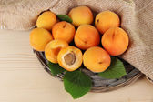 Apricots on wicker coasters on wooden table — Stock Photo
