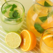 Orange and lemon lemonade in pitchers and glasses on wooden table close-up — Foto Stock