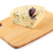 Tasty blue cheese on cutting board, isolated on white — Stock Photo