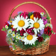 Beautiful bright flowers in wicker basket on table on pink background — Stock Photo #26492367