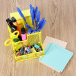 Office equipment in yellow stationary holder on beige wooden table — Stock Photo