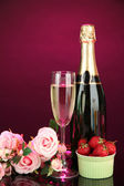 Romantic still life with champagne, strawberry and pink roses, on dark color background — Stock Photo