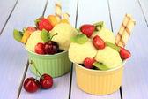 вкусное мороженое с фруктами и ягодами в чашу на деревянный стол — Стоковое фото