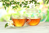 Cup of tea with jasmine, on wooden table, on bright background — Stock Photo
