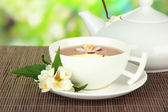 Cup of tea with jasmine, on bamboo mat, on bright background — Stock Photo