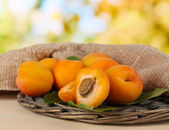 Apricots on wicker coasters on wooden table on nature background — Stock Photo