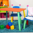 Small and colorful table and chairs with baby clothes — Stock fotografie