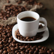 Cup of coffee and coffee beans on wooden background — ストック写真