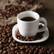 Cup of coffee and coffee beans on wooden background — Foto Stock