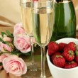Romantic still life with champagne, strawberry and pink roses, on color fabric background — Stock Photo
