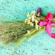 Stock Photo: Bouquet of wild flowers and herbs, on color wooden background