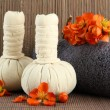 Herbal compress balls for spa treatment and towel on bamboo background — Stock Photo #26547263