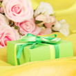 Stock Photo: Beautiful gift on flowers background