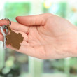 Key with leather trinket in hand on window background — Stock Photo