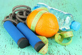 Orange with measuring tape,skipping rope and bottle of water, on color wooden background — Stock Photo