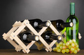 Bottles of wine placed on wooden stand on grey background — Stock Photo