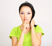 Girl shows sign of silence on grey background — Stock Photo