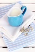 Blue jug with milk on napkin on wooden picnic table close-up — Stock Photo