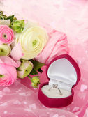 Ranunculus (persian buttercups) and engagement ring, on pink cloth — Stockfoto