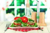 Savoureuses tranches de moelle et tomates rôties avec des feuilles de salade, sur fond clair — Photo
