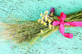 Bouquet of wild flowers and herbs, on color wooden background — Stock Photo