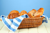 Composition with buns in wicker basket, on wooden table, on color background — Stock Photo