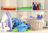 Clothes and iron on table on shelves background — Stock Photo