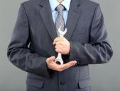 Joven empresario con llave en fondo gris — Foto de Stock