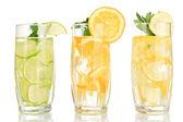Copos de bebidas de frutas com cubos de gelo, isolados no branco — Fotografia Stock