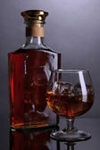 Brandy glass with ice and bottle on grey background — Stock Photo
