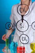 Chemist woman writing formulas on glass on blue background — Stock Photo