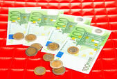 Euro banknotes and euro cents on red background — Stock Photo