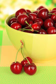 Cherry berries in bowl on table on bright background — Stock Photo