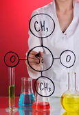 Chemist woman writing formulas on glass on red background — Foto Stock