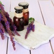 Stock Photo: Medicine bottles and salviflowers on purple wooden background