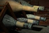 Vieilles bouteilles de vin dans l'ancienne cave, sur fond foncé — Photo