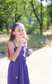Cute girl blowing soap bubbles outdoors — Stock Photo