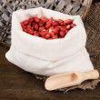 Peanuts in sack on wooden background — Stock Photo #26591341