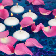 Rose petals and candles in water in vase on blue background close-up — Foto Stock