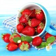 Ripe sweet strawberries in cup on blue wooden table — Stock Photo