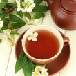 Cup of tea with jasmine, on wooden table, close-up — Stock Photo