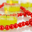 Lighted candles with beads close up — Stock Photo #26594085
