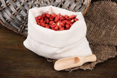 Peanuts in sack on wooden background — Stock Photo