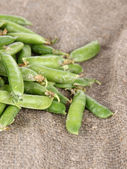 Green peas on bagging background — Stock Photo