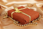 Romantic parcel on gold cloth background — Stock Photo
